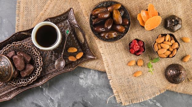 日付のフルーツとアーモンドの金属製トレイの上のコーヒーカップ 無料写真
