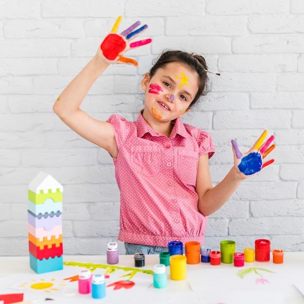 カラフルな色のテーブルの前に立っている塗装手を示すかわいい女の子 無料写真