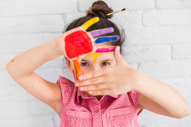 白いレンガの壁に立っている彼女の塗られた手を通して見る少女の肖像画 無料写真