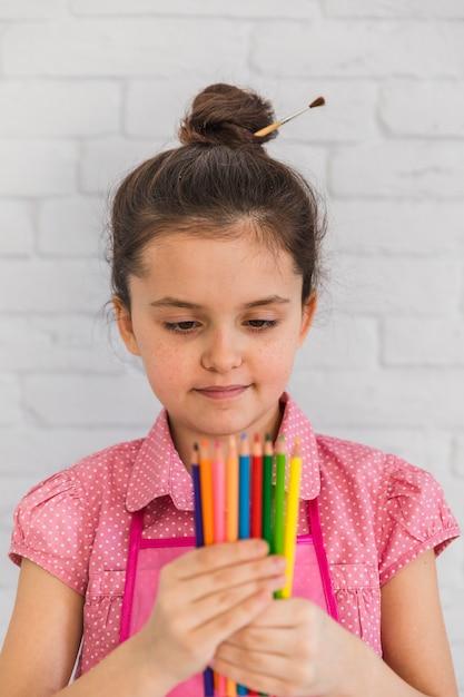 色とりどりの鉛筆を手で見ている少女の肖像画 無料写真