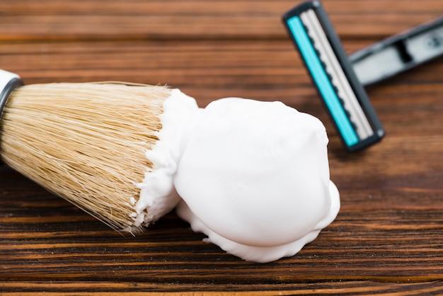 Бритва и кисточка для бритья с пеной на деревянном фоне Бесплатные Фотографии