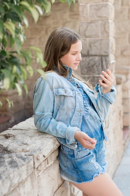 Девочка-подросток, опираясь на стену, глядя на мобильный телефон Бесплатные Фотографии