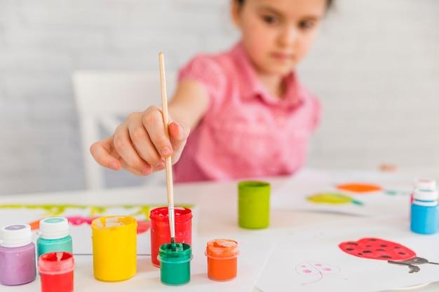 Селективный фокус девушки вставляя кисть в красочной бутылке на белом столе Бесплатные Фотографии
