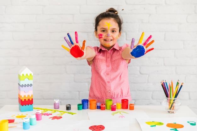 カメラに彼女の塗られたカラフルな手を見せて女の子の肖像画を笑顔 無料写真