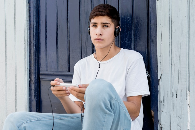 考えている少年が携帯電話で音楽を聴く 無料写真