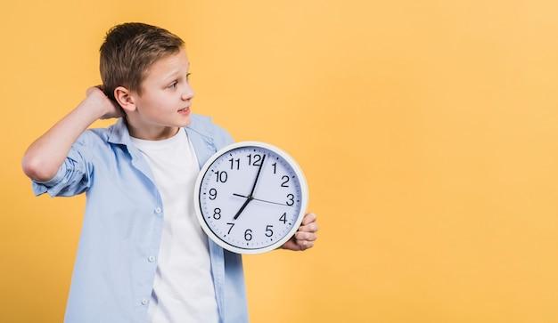 Рассматриваемый мальчик держит белые часы в руке, глядя в сторону Бесплатные Фотографии
