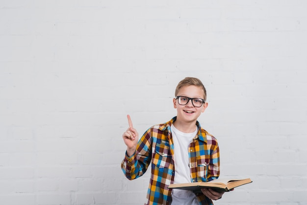 開いた本を手に持って眼鏡を持つ微笑む少年の肖像画 無料写真