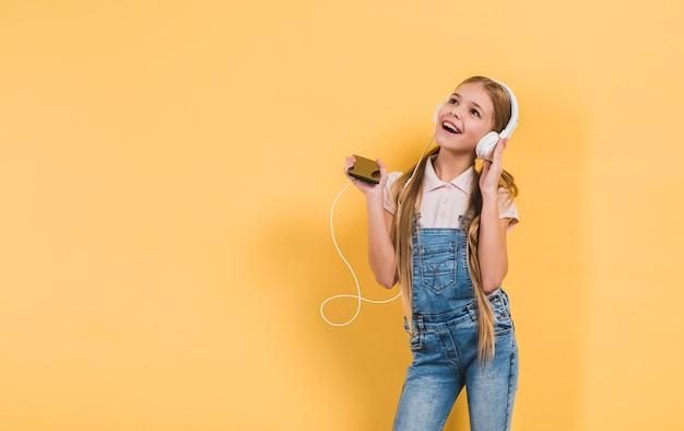 手に黄色の背景に対して立っている携帯電話を保持しているヘッドフォンで音楽を楽しんで幸せな女の子 無料写真