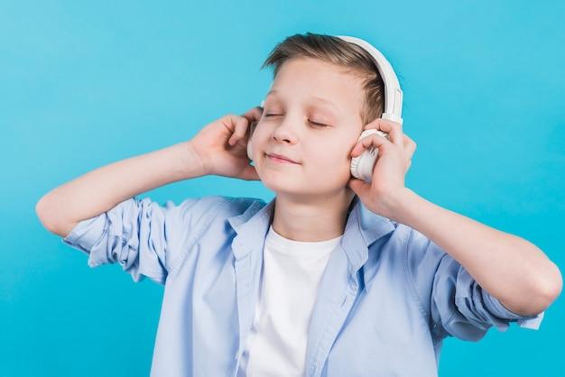 青い背景に白いヘッドフォンで音楽を聴くを楽しむ少年のクローズアップ 無料写真