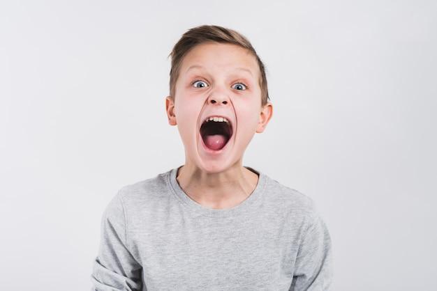 灰色の背景に対して大声で叫んでいる少年の肖像画 無料写真