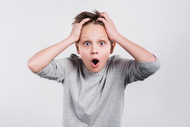 灰色の背景に対してカメラを探している頭の上の彼の手でショックを受けた少年の肖像画 無料写真