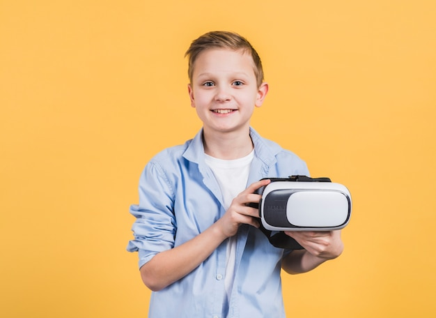 黄色の背景に対して手で仮想現実の眼鏡を持つ男の子の肖像画を笑顔 無料写真