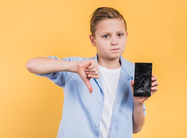 黄色の背景に対して親指を表示ひびの入った画面でスマートフォンを持つ男の子の肖像画 無料写真