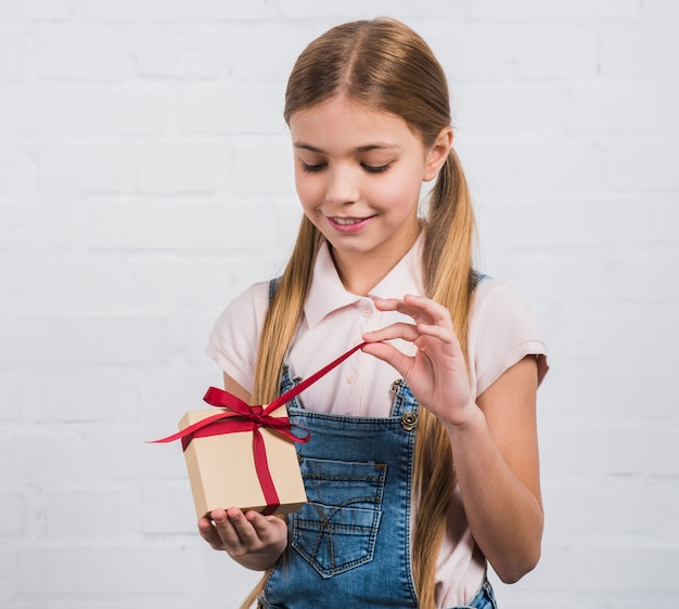 Усмехаясь портрет девушки раскрывая подарочную коробку стоя против белой кирпичной стены Бесплатные Фотографии