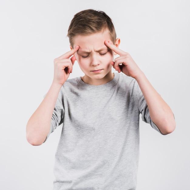 白い背景に対して立っている頭痛を持つ深刻な少年 無料写真