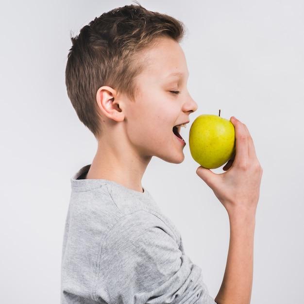 白い背景に分離された緑の新鮮なリンゴを食べる少年の側面図 無料写真