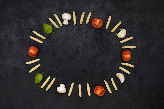 未調理のガルガネリパスタで作られた空の円形フレーム。トマト;キノコ;ニンニクとバジルの黒の織り目加工の背景 無料写真