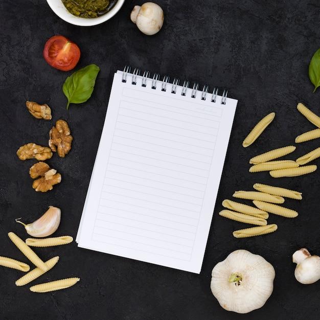 ガルガネリパスタと空白のスパイラルメモ帳の上から見る。クルミ;バジル;トマト;キノコとニンニクが黒の背景にクローブ 無料写真