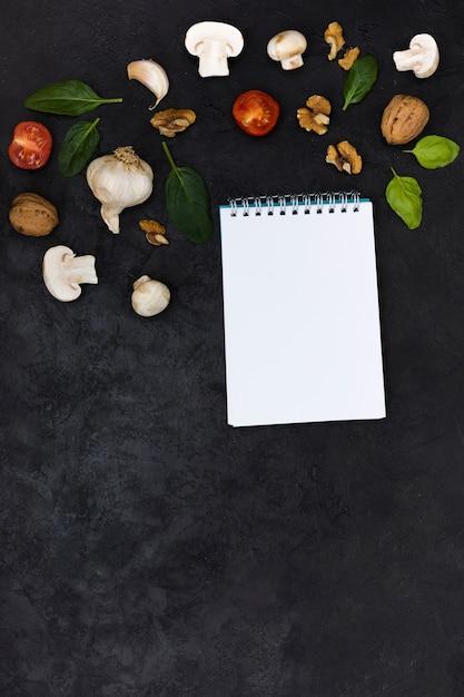 黒の織り目加工の背景に対して空白の白いスパイラルメモ帳の上のピザ成分 無料写真