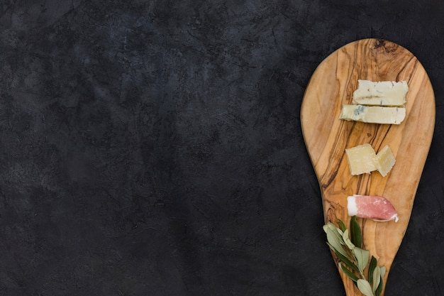 Вид сверху на сыр; веточка с беконом и оливками на разделочной доске на черном фоне Бесплатные Фотографии