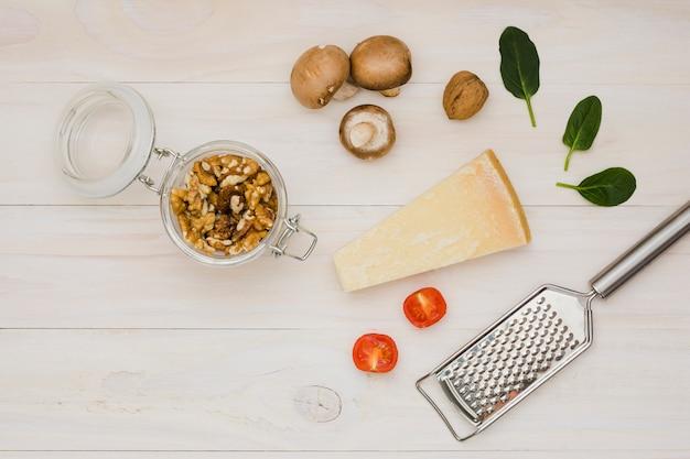 クルミトマト;チーズ;バジルとキノコの木製の机の上の金属のおろし金 無料写真