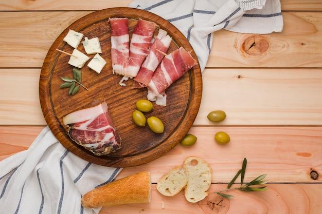 Поднятый вид бекона; маслины; ломтики сыра и хлеба на деревянной круглой доске над столом Бесплатные Фотографии