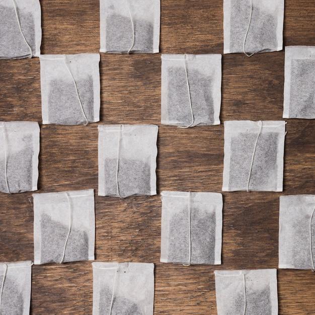 木製の織り目加工の背景に市松模様のティーバッグ 無料写真