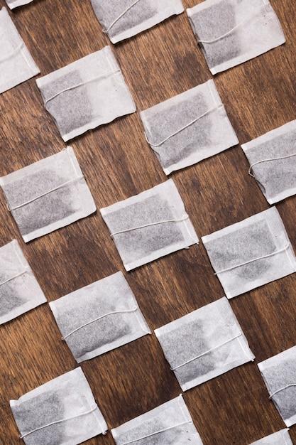 Скрещенный белый чай в пакетиках на деревянном текстурированном фоне Бесплатные Фотографии
