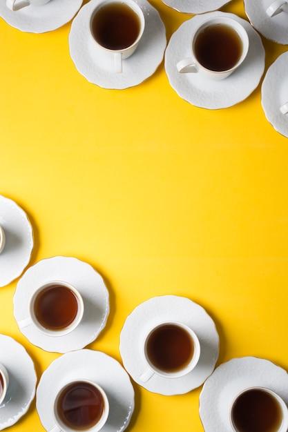 Чашка травяного чая и блюдца на углу желтого фона Бесплатные Фотографии