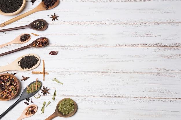 白い木製のテーブルの上の木のスプーンでスパイスの立面図 無料写真