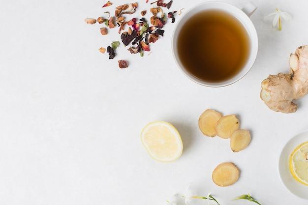 Чашка травяного чая с лимоном; имбирь; ингредиенты из цветов и сухих лепестков на белом фоне Бесплатные Фотографии