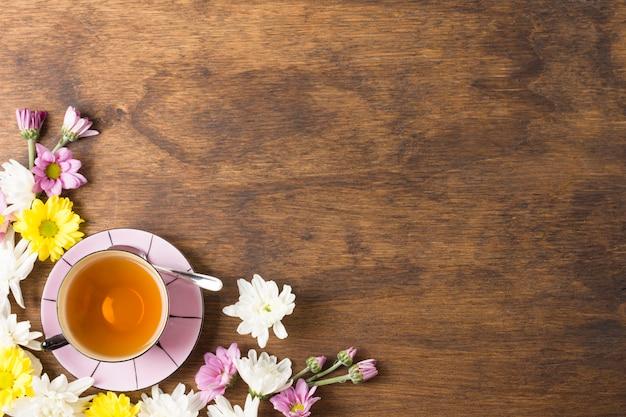 ハーブティーカップと木製の背景の隅に美しい花 無料写真