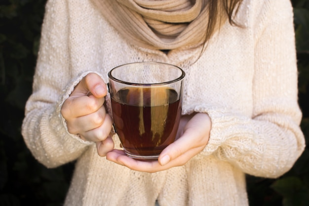 ハーブティーの透明なコップを保持している若い女性のクローズアップ 無料写真
