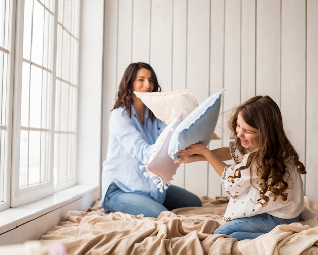 母と娘の枕で遊んで 無料写真