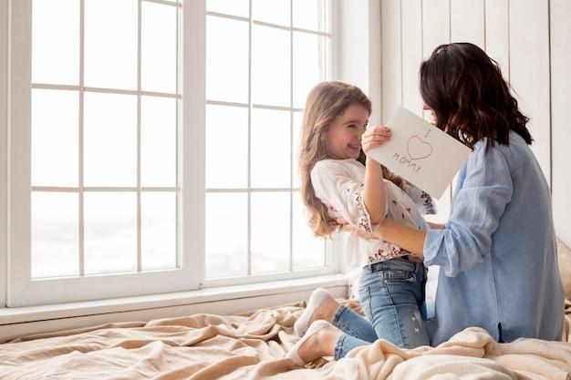 Счастливая мать обнимает дочь с поздравительной открытки Бесплатные Фотографии