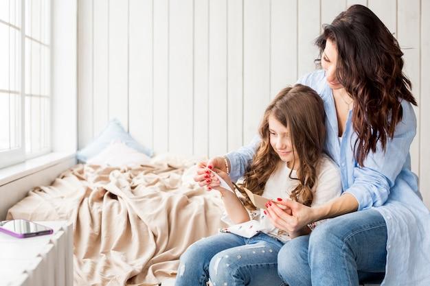 母とかわいい娘のグリーティングカードを読む 無料写真