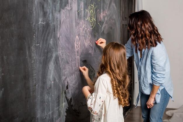 母と娘が黒板に描く 無料写真