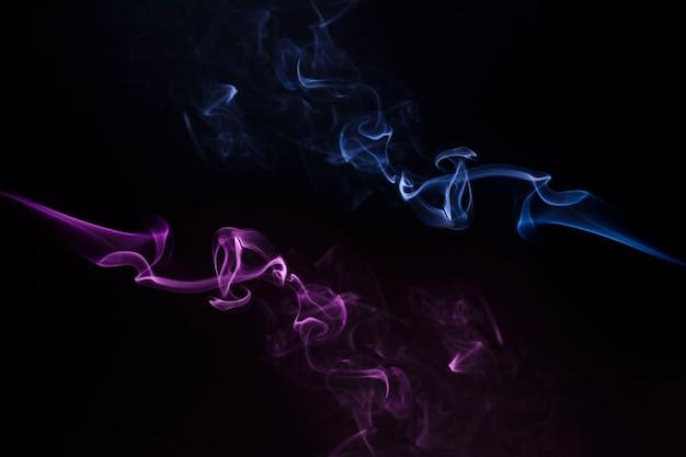 黒を背景に旋回する青と紫の煙のクローズアップ 無料写真