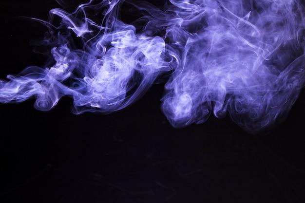 Движение мягкого фиолетового дыма на черном фоне Бесплатные Фотографии