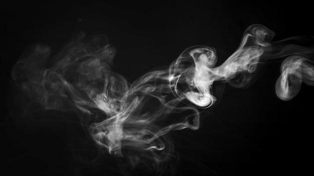 黒の背景の前に厚いきらめく煙パターン 無料写真