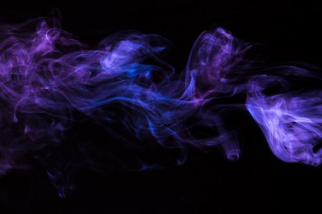 黒の背景に紫の煙の動きのクローズアップ 無料写真