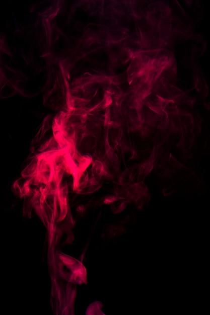黒の背景に広がる赤い煙の動き 無料写真