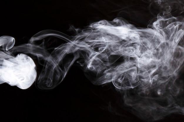 黒の背景に白の密な旋回煙 無料写真