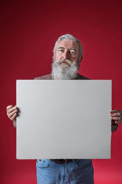 赤い背景に対して空白の白いプラカード立っているを示す年配の男性人の肖像画 無料写真