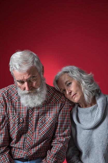 色付きの背景に対して意気消沈した年配のカップル 無料写真
