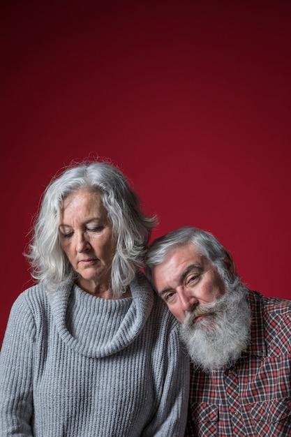 赤い背景に対して彼の妻の肩にもたれて悲しい年配の男性 無料写真