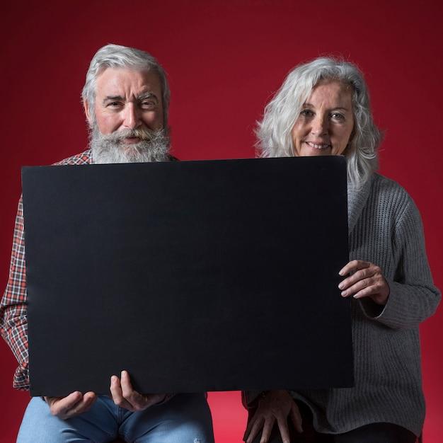 赤い背景に対してカメラを探している黒いプラカードを持って幸せな先輩カップルの肖像画 無料写真