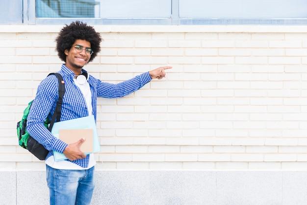 白い塗られた壁に指を指している手で本を持っているアフリカの笑みを浮かべて男子学生の肖像画 無料写真