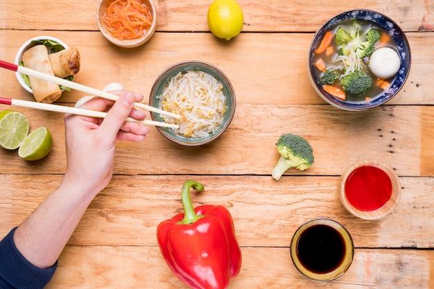 テーブルの上の箸でもやしを食べる人の手のクローズアップ 無料写真