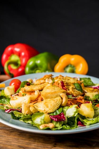 チキンのおいしいサラダ。ナッツ;と黒の背景に机の上の野菜 無料写真